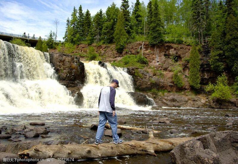 登山的男人穿过瀑布的人图片
